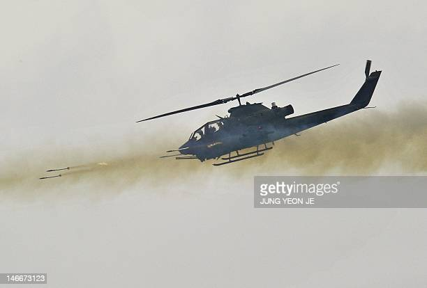 A South Korean AH1S Cobra helicopter fires rockets during a joint live firing drill with the US at the Seungjin Fire Training Field in Pocheon 65 kms...