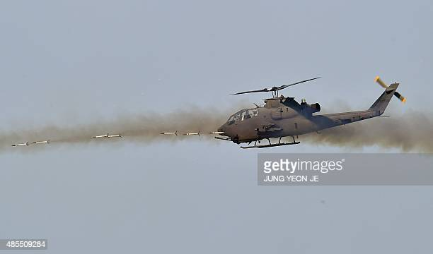 A South Korean AH1S Cobra helicopter fires rockets during a joint live firing drill between South Korea and the US at the Seungjin Fire Training...