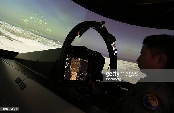 South Korean Air Force soldier tries out a Boeing Co. F-15 jet simulator at the Seoul International Aerospace & Defense Exhibition 2013 in Goyang,...