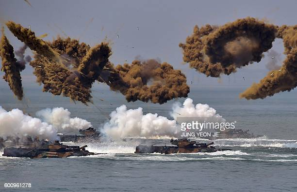 TOPSHOT South Korean amphibious vehicles fire smoke shells during a reenactment of the Incheon landing to mark the 66th anniversary of the start of...