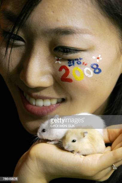 A South Korean amusement park worker shows hamsters on her hand during an event to mark the upcoming Year of the Rat at the Everland Amusement and...
