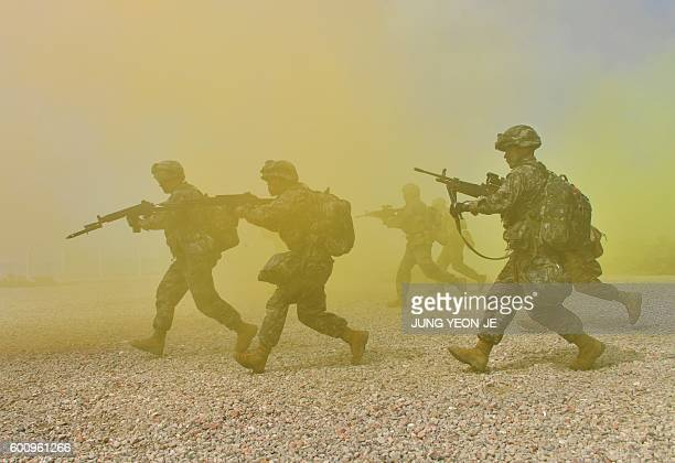 South Korean and US marines move to a position during a re-enactment of the Incheon landing to mark the 66th anniversary of the start of Operation...