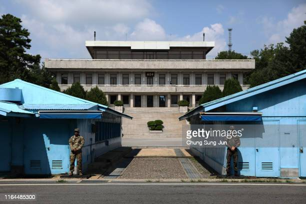 South Korean and US soldier stand guard at the border village of Panmunjom between South and North Korea during a ceremony to commemorate the 66th...
