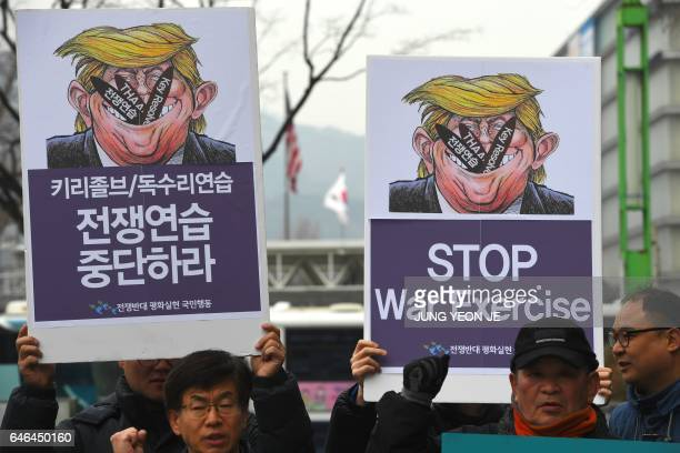 South Korean antiwar activists hold placards showing a caricature of US President Donald Trump during a rally against South KoreaUS joint military...