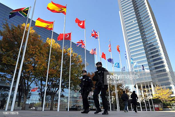 South Korean armed walk past flags as they patrol ouside the venue of the G20 Summit in Seoul on November 9 2010 In response to expected protests for...