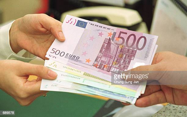 South Korean bank employee gives change in euro banknotes January 2 2002 at the headquarters of the Korea Exchange Bank in Seoul South Korea South...