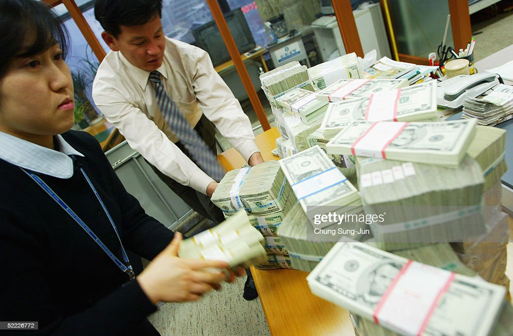South Korean bankers carry US dollar bank notes at the Korea Exchange bank on February 22, 2005 in Seoul, South Korea. The South Korean won jumped to its highest intraday level in more than seven years in domestic trade on Tuesday, boosted by strong foreign equity buying and exporter deals.