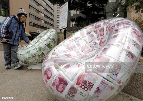 South Korean boy looks plastic chairs showing packs of the EURO and the Chinese yuan outside the Korea Exchange Bank in Seoul 31 January 2006 Bank...