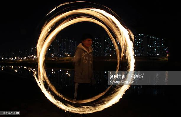 South Korean boy spins a fire can during 'Jwibulnoli' a South Korean folk game at Han River on February 23 2012 in Seoul South Korea The event is...
