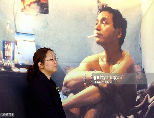 South Korean Buddhist fan of canto pop singer and actor Leslie Cheung prays in front of his portrait during a memorial service at the Bongun Temple...