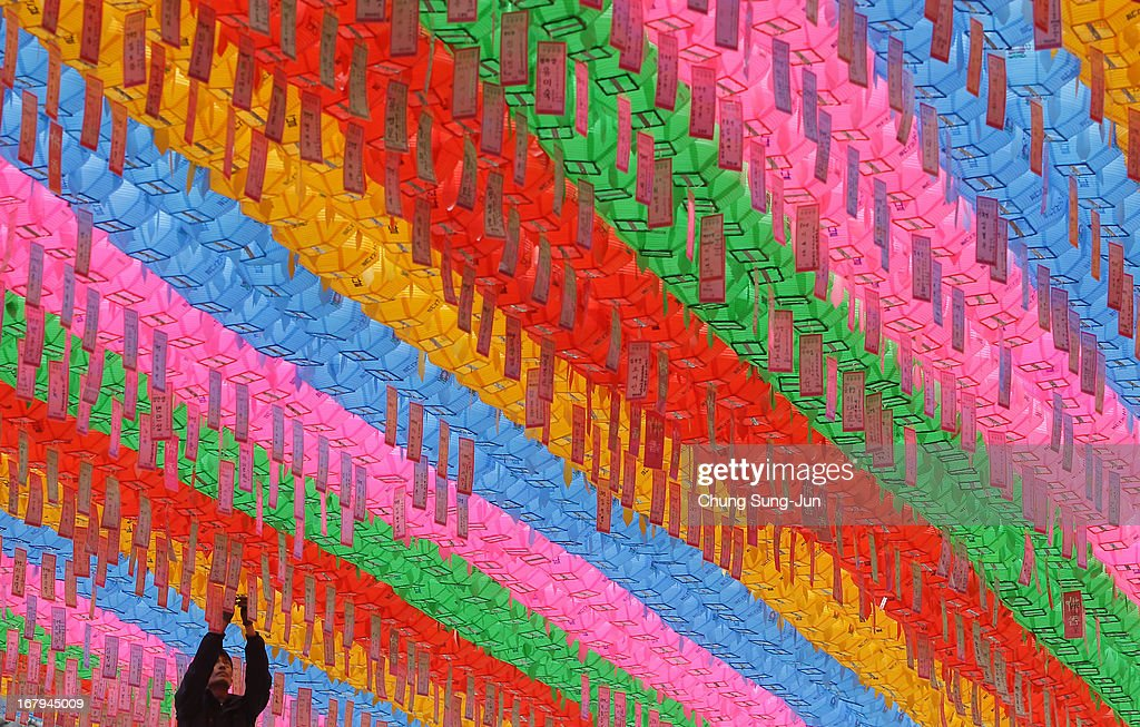 A South Korean Buddhist hangs colourful lanterns to celebrate the forthcoming birthday of Buddha at the Chogye temple on May 3, 2013 in Seoul, South Korea. Buddha was born approximately 2,557 years ago, and although the exact date is unknown, Buddha's official birthday is celebrated on the full moon in May in South Korea, which is on May 17 this year.