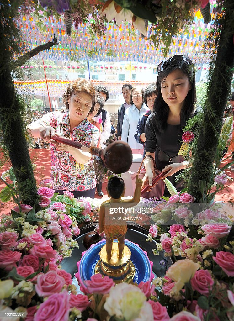 South Korean Buddhists pour water on a small statue of Buddha during a service to celebrate the 2,554th birthday of Buddha at Chogye temple in Seoul on May 21, 2010. South Korean Buddhists hold several events to celebrate Buddha's birthday.