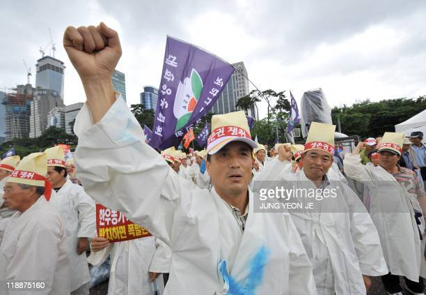 South Korean cattle farmers and other farmhouse workers shout slogans during a rally to oppose the ratification of a free trade pact with the US near...