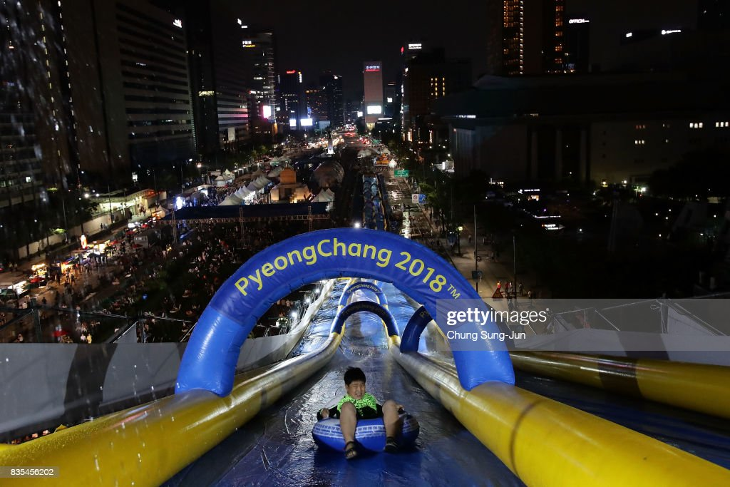 A South Korean child slides down on an inflatable ring during the 'Bobsleigh In the City' on August 19, 2017 in Seoul, South Korea. The 22-metre-high 300-metre-long water slider has been set up in the central Seoul to promote upcoming PyeongChang Winter Olympics.