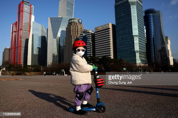 South Korean child wears a mask to prevent catching the coronavirus while riding a scooter on February 27, 2020 in Seoul, South Korea. The government...