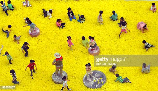 South Korean children play on a field of large plastic coins and cash deposit bags in a park in Seoul on May 5 2010 South Korea's economy grew a...