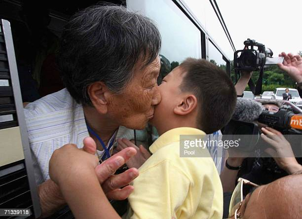 South Korean Choi GyeWol kisses her grandson Kim CholBong goodbye as her son Kim YoungNam watches before she returns to her South Korean home after...