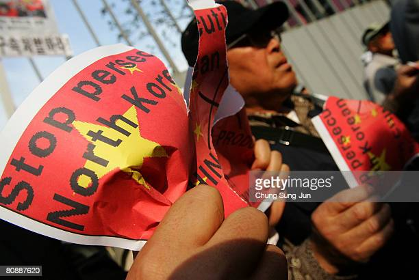 South Korean civic group members protesting at an antiChinese rally symbolically rip the Chinese flag printed on the background of placards featuring...