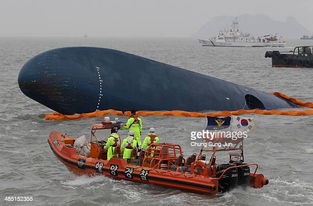 South Korean Coast Guard and rescue teams search for missing passengers at the site of the sunken ferry off the coast of Jindo Island on April 17...