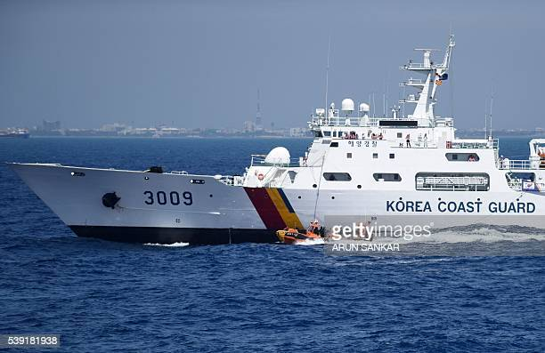 South Korean coastguard troops sprint on a speed boat during a hijacking scenario involving a merchant vessel during the IndoKorea joint coastguard...