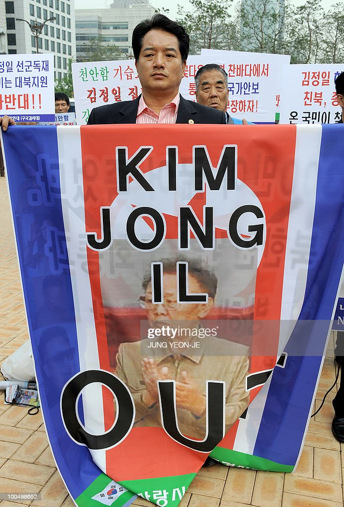A South Korean conservative activist holds a North Korean flag showing a picture of its leader Kim Jong-Il during an anti-North Korea rally in Seoul on May 25, 2010 after South Korea announced reprisals against North Korea for the sinking of a warship. North Korean leader Kim Jong-Il ordered troops and civil organisations on combat alert after South Korea accused his country of sinking a warship, a defector group said.