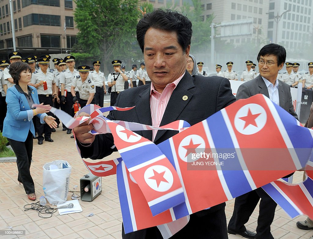 A South Korean conservative activist tears up prints of a North Korean flag during an anti-North Korea rally in Seoul on May 25, 2010 after South Korea announced reprisals against North Korea for the sinking of a warship. North Korean leader Kim Jong-Il ordered troops and civil organisations on combat alert after South Korea accused his country of sinking a warship, a defector group said.