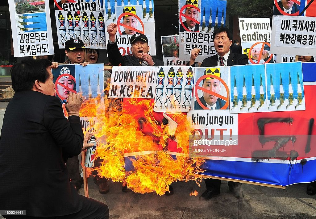 South Korean conservative activists burn a North Korean flag during a rally denouncing North Korea's missile test-launch in Seoul on March 26, 2014. North Korea test-fired two medium-range ballistic missiles on March 26, prompting a stern US reaction after President Barack Obama hosted a landmark Japan-South Korea summit aimed at uniting the three nations against Pyongyang's nuclear threat.