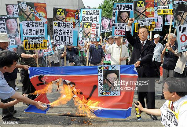 South Korean conservative activists burn a North Korean flag whilst holding protest placards showing the crossedout face of North Korean leader Kim...