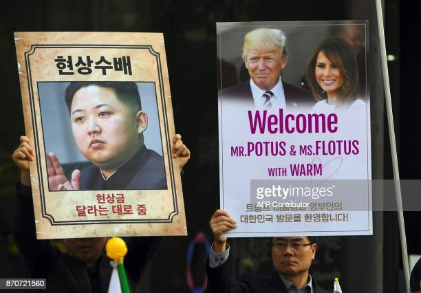 South Korean conservative activists hold placards showing pictures of North Korean leader Kim JongUn and US President Donald Trump and his wife...