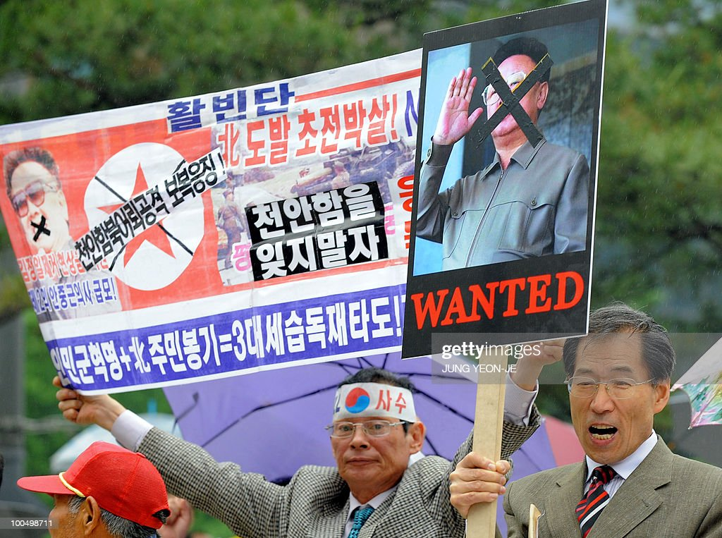South Korean conservative activists hold up placards showing defaced portrait of North Korean leader Kim Jong-Il during an anti-North Korea rally in Seoul on May 25, 2010 after South Korea announced reprisals against North Korea for the sinking of a warship. North Korea's military accused the South Korean navy of trespassing in its waters and threatened military action in response. The Korean letters read 'Crush North Korea's provocation at the beginning!'