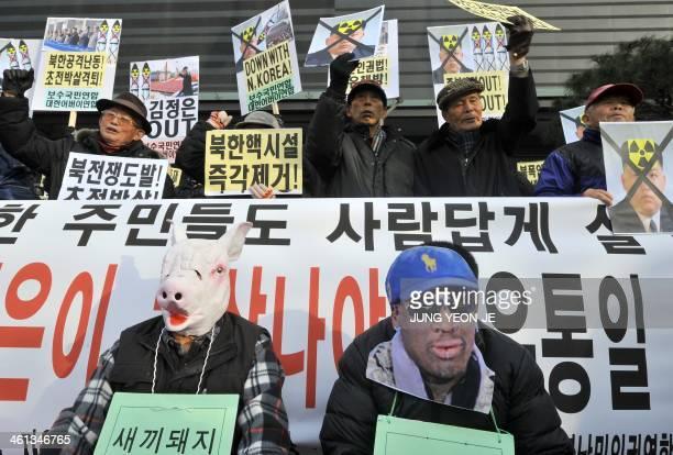 South Korean conservative activists wear masks of a pig symbolizing North Korean leader Kim JongUn and former NBA star Dennis Rodman during an...