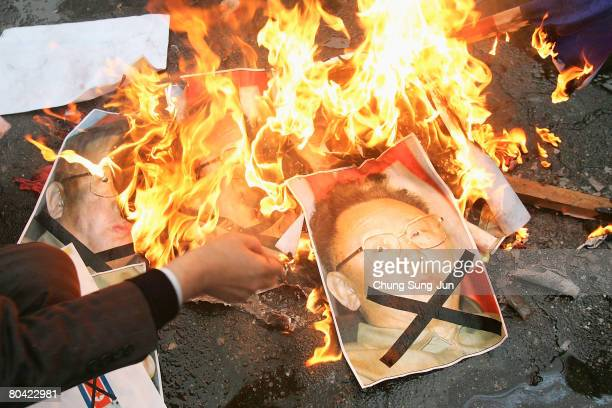 South Korean conservative protesters burn a North Korean flag and portraits of North Korean leader Kim JongIl during a rally against the North Korea...