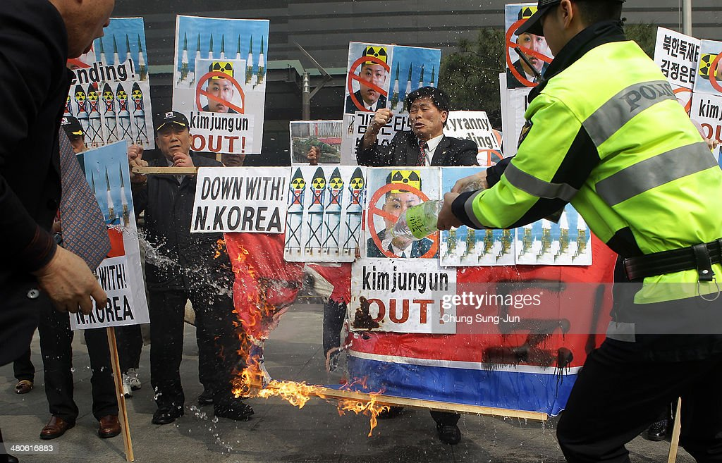 South Korean conservative protesters burn North Korea's flag as South Korean policemen spray water during a anti-North Korea rally on March 26, 2014 in Seoul, South Korea. North Korea test-launched two Nodong medium-range ballistic missiles into the sea off Korean peninsula's east coast on Wednesday morning, according to South Korea's defence ministry.