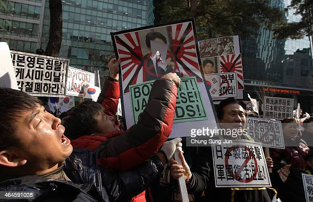 South Korean conservative protesters destroy Japanese military placards during a demonstration as South Korea marks the forthcoming 96th Independence...