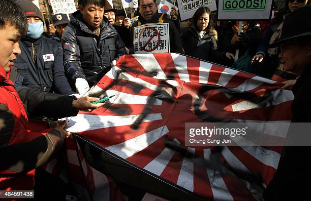 South Korean conservative protesters destroy Japanese military flags during a demonstration as South Korea marks the forthcoming 96th Independence...