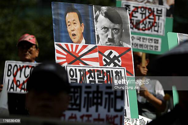 South Korean conservative protesters hold antiJapan placards during demonstrations as South Korea marks the 68th Independence Day in front of the...