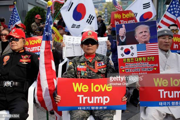 South Korean conservative welcomes US President Donald Trump hold We love Trump banners during a proTrump rally on November 4 2017 in front of US...