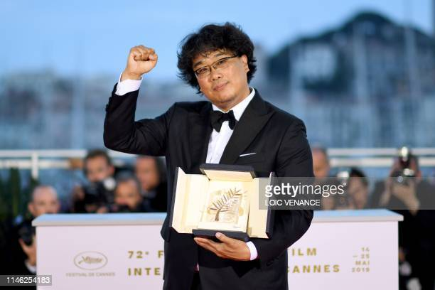South Korean director Bong JoonHo poses during a photocall with his trophy after he won the Palme d'Or for the film Parasite on May 25 2019 during...