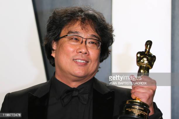 "South Korean director Bong Joon-ho poses with the Oscar for Best Screenplay for ""Parasite"" as he attends the 2020 Vanity Fair Oscar Party following..."