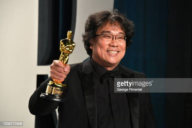South Korean director Bong Joonho poses with the Oscar for Best Screenplay for Parasite as he attends the 2020 Vanity Fair Oscar party hosted by...