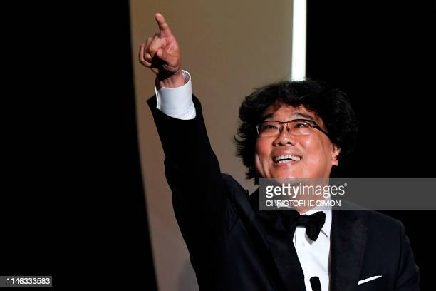 South Korean director Bong JoonHo reacts on stage after he was awarded with the Palme d'Or for the film Parasite on May 25 2019 during the closing...