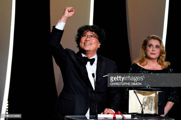 South Korean director Bong JoonHo reacts on stage next to French actress Catherine Deneuve after he was awarded with the Palme d'Or for the film...