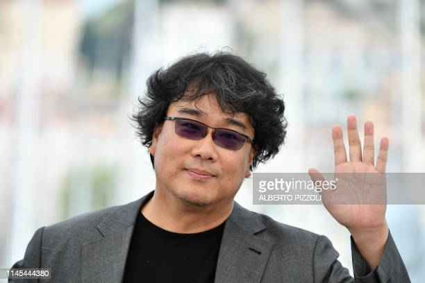 South Korean director Bong JoonHo waves during a photocall for the film Parasite at the 72nd edition of the Cannes Film Festival in Cannes southern...