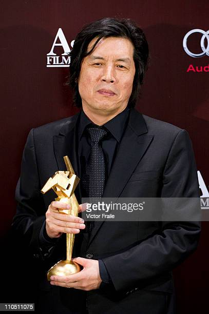 South Korean director Lee Changdong poses backstage after winning the Best Director Award for his work at the 'Poetry' during the 5th Asia Film...