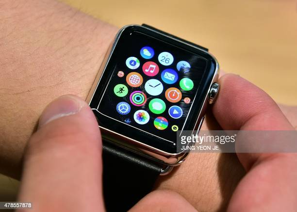 A South Korean employee shows the 'Apple Watch' at an Apple shop in Seoul on June 26 2015 Apple Watch on June 26 arrived in seven more countries...