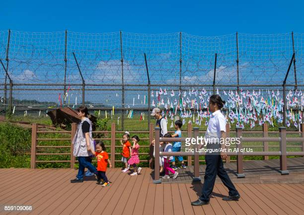 South Korean family passing in front of messages of peace and unity written on ribbons left on fence at DMZ North Hwanghae Province Panmunjom South...