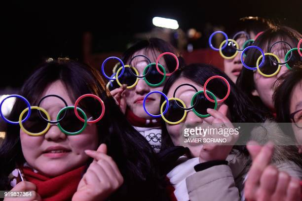 TOPSHOT South Korean fans wearing sunglasses shaped like the Olympic rings attend medal ceremonies at the Pyeongchang Medals Plaza during the...