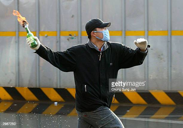 South Korean farmer hurls a fire bomb at riot police during an anti-government rally against the controversial bill on the free trade agreement with...