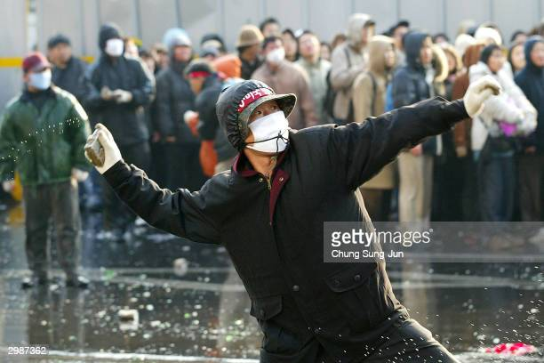 South Korean farmer hurls a rock at riot police during an anti-government rally against the controversial bill on the free trade agreement with...