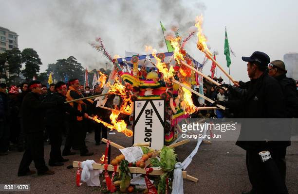 South Korean farmers burn a figure of a symbolizing AntiFTA during a rally objecting to South Korea's Free Trade Agreement with the USA near the...